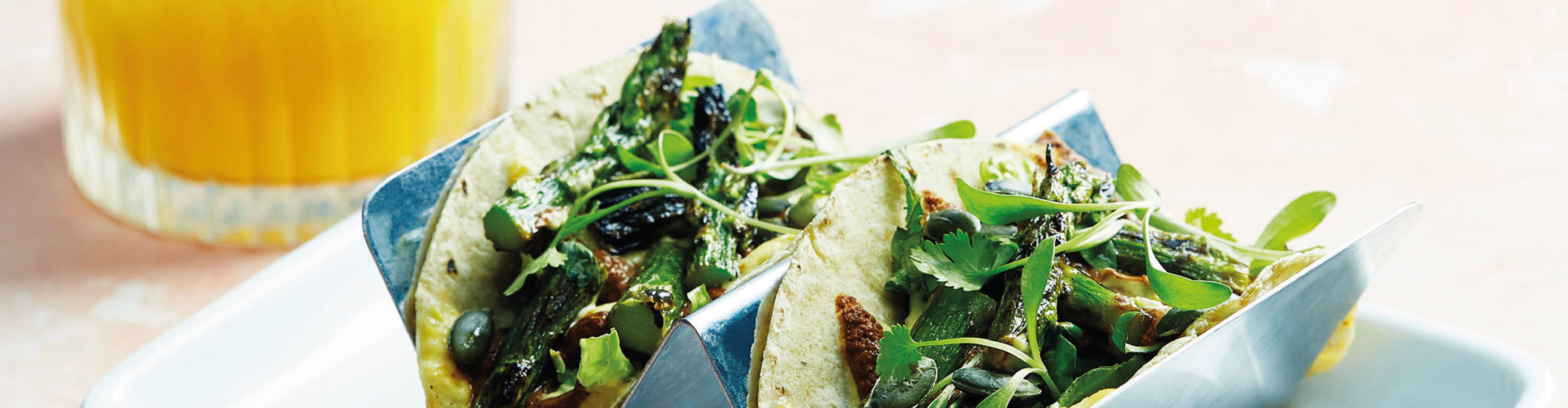 Two soft corn tortillas bursting with vibrant, green, seasonal, asparagus spears, displayed in a taco wave