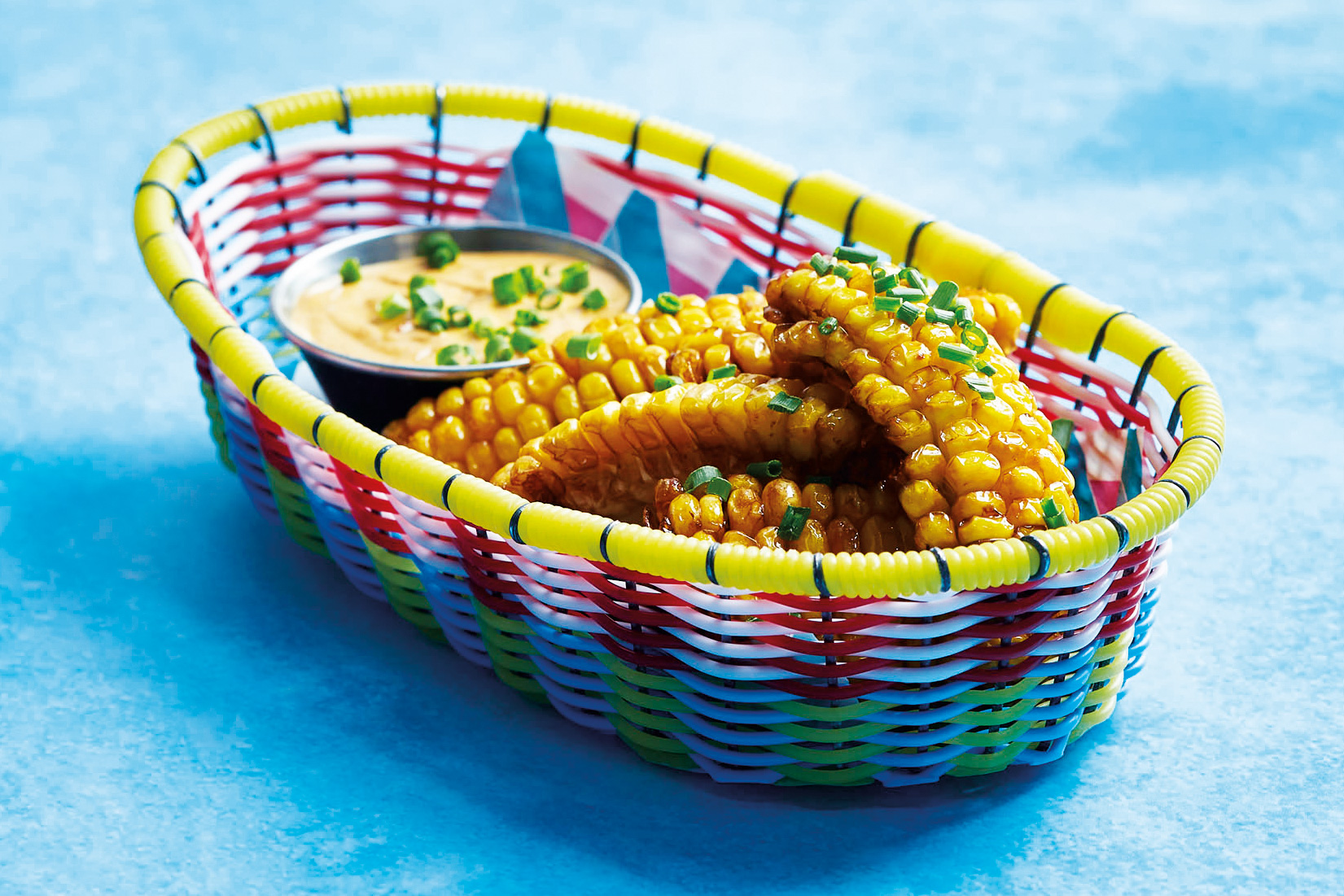 Corn ribs served in a colourful basket with a chipotle mayo on the side